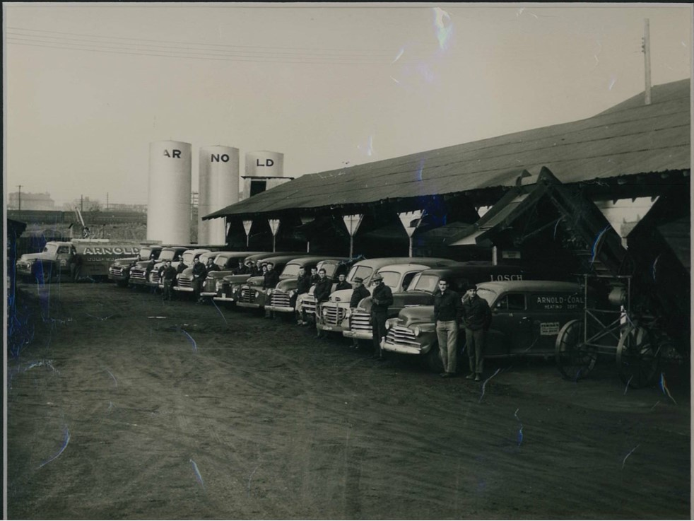 Arnold Coal and Supply 1940, our parent company, pictured with delivery trucks, drivers, and storage tanks.
